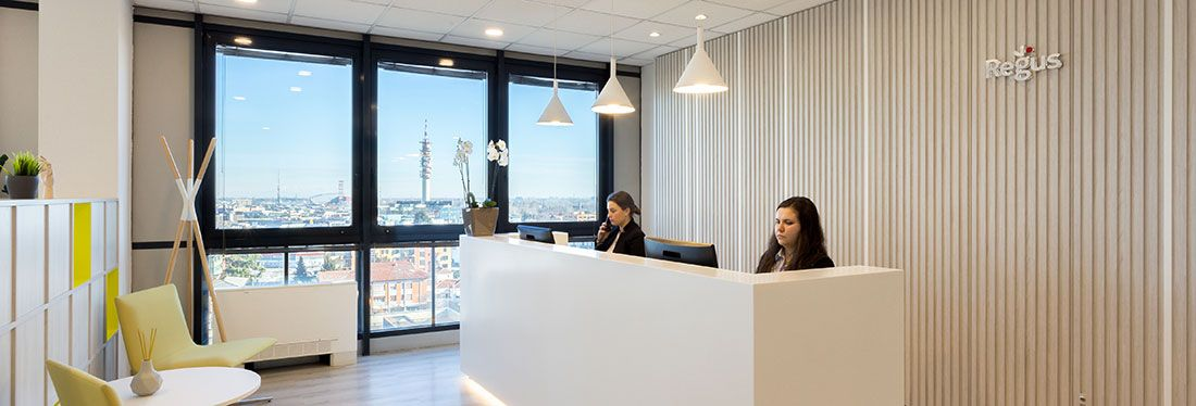 Two women working at the reception of a Regus office